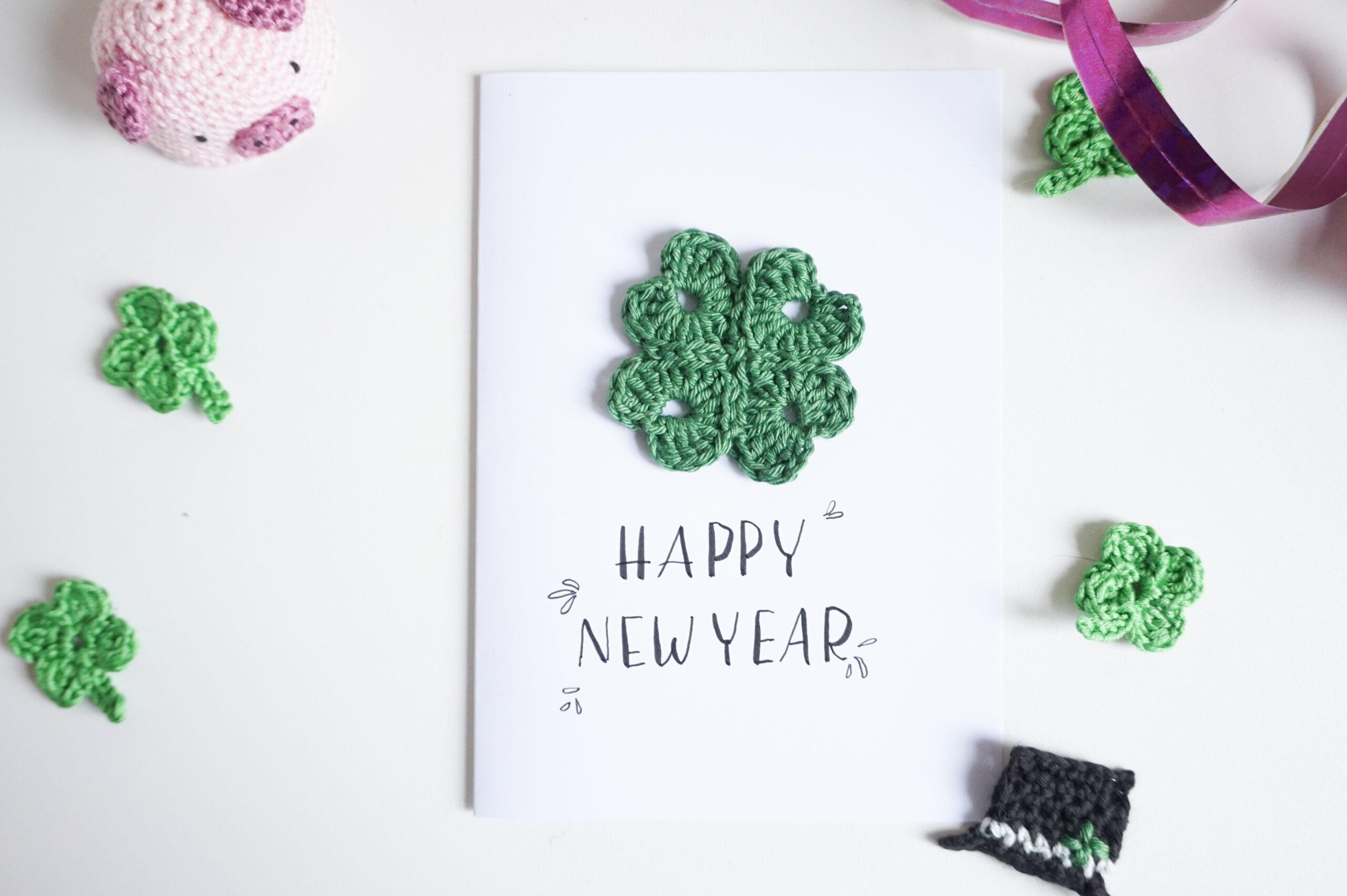 Gehäkeltes Kleeblatt auf einer Glückwunschkarte zum Neuen Jahr