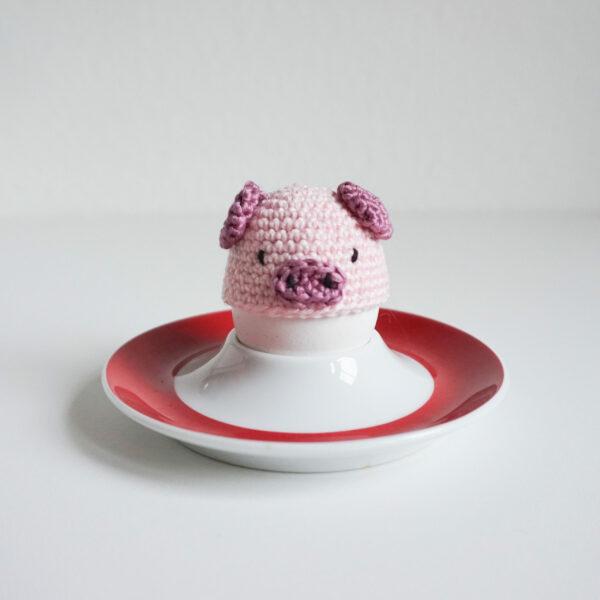 Gehäkelter Eierwärmer Glücksschwein auf einem Ei im Eierbecher