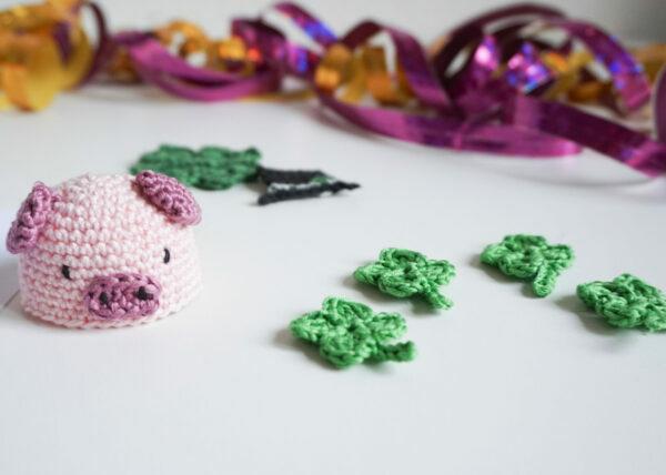 Gehäkelter Eierwärmer in Form eines Glücksschweins und kleine gehäkelte Kleeblätter.