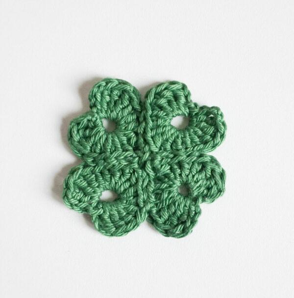Gehäkeltes Kleeblatt, das sich aus vier Herzen zusammensetzt.