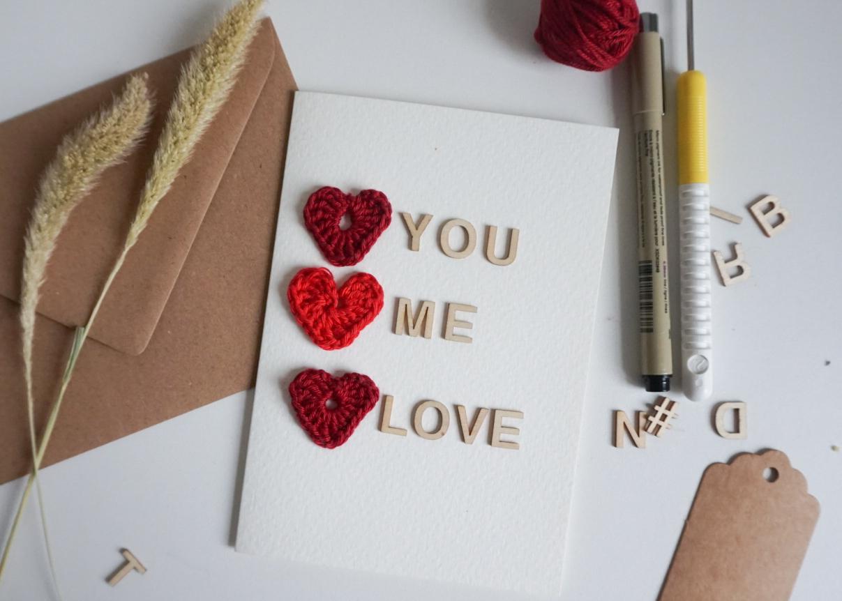 Das Bild zeigt eine Klappkarte zum Valentinstag mit den Worten you me love und drei gehäkelten Herzen