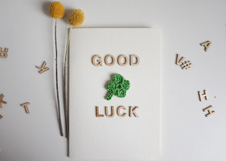 """Karte mit einem gehäkelten Kleeblatt und dem Schriftzug """"Good luck"""" aus Holzbuchstaben"""