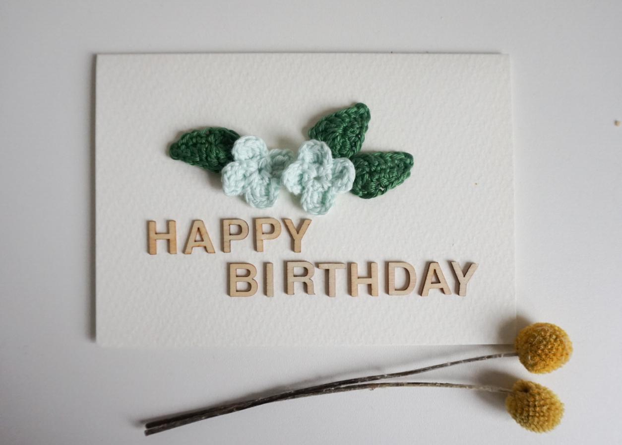 """Geburtstagskarte mit gehäkelten Blüten und Blättern sowie dem Schriftzug """"Happy Birthday"""" aus Holzbuchstaben"""